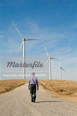 Homme marchant vers les turbines de vent