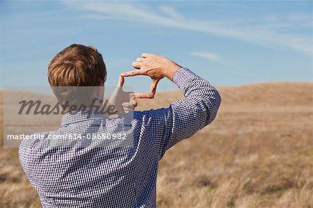 Mann mit Händen zu Frame-Landschaft