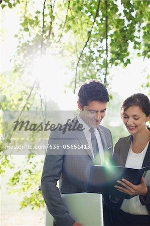 Gens d'affaires en regardant rapport ensemble en plein air