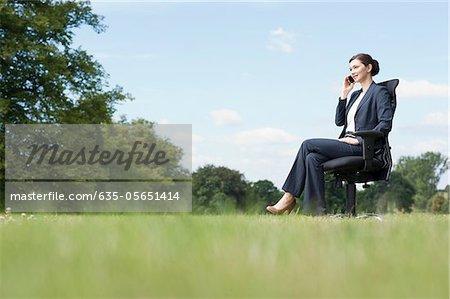 Femme d'affaires assis dans la chaise parlait au téléphone cellulaire à l'extérieur