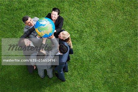 Geschäftsleute heben Globus zusammen im freien
