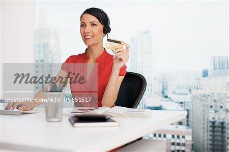 Geschäftsfrau, Besitz von Kreditkarte am Schreibtisch