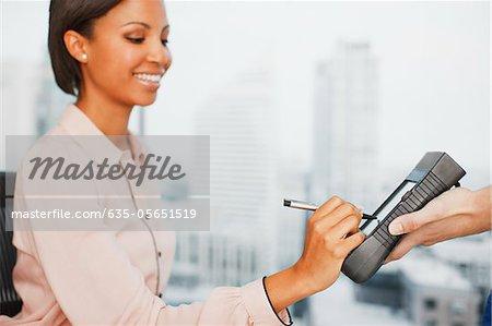 Femme écrivant de signature sur dispositif électronique