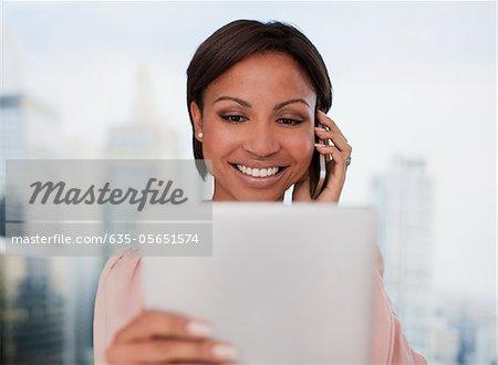 Geschäftsfrau holding digital Tablet und Gespräch am Handy