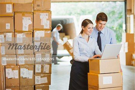 Gens d'affaires à l'aide d'ordinateur portable en entrepôt
