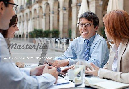 Gens d'affaires travaillant ensemble dans le café de trottoir