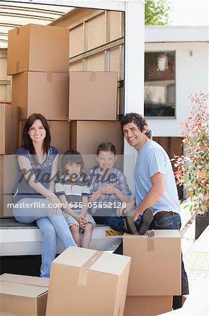 Famille assis l'arrière du camion de déménagement