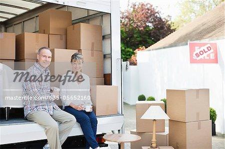 Couple de boire du café sur l'arrière du camion de déménagement