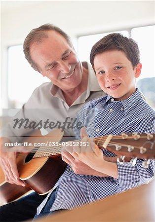 Grand-père petit-fils à jouer de la guitare d'enseignement