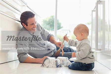 Vater und Sohn spielen mit Töpfen und Holzlöffel