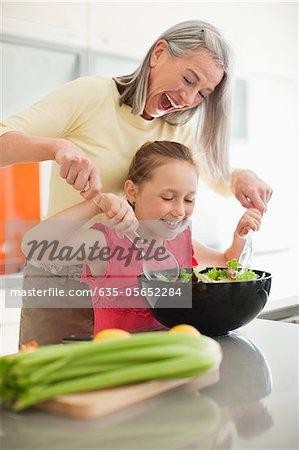 Grandmother and granddaughter preparing salad together