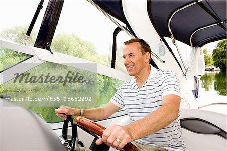 Man steering boat on river