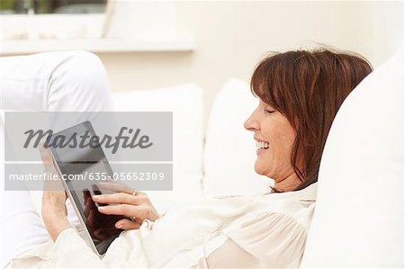 Frau sitzt auf dem Sofa mit digitalen tablet