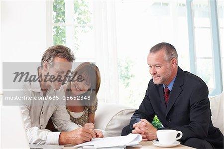 Paar Unterzeichnung Vertrag mit Finanzberater