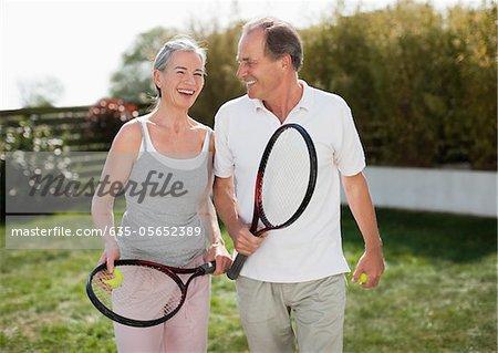 Couple tenant à l'extérieur des raquettes de tennis