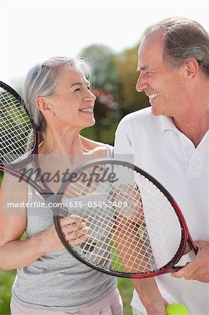 Couple souriant sourire tenir des raquettes de tennis