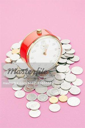 Ein Wecker und Münzen