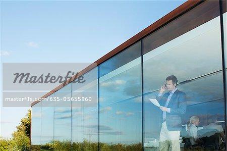 Kaufmann mit Papierkram am Handy in Bürofenster sprechen