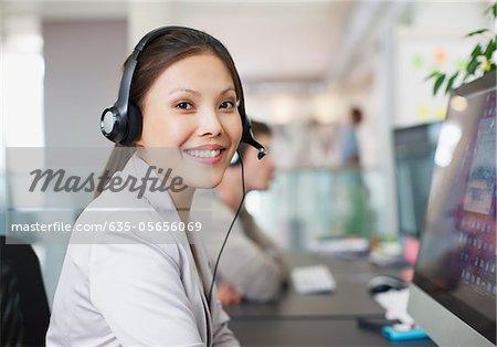 Porträt von lächelnd geschäftsfrau mit Headset am Computer im Büro