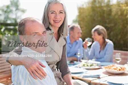 Portrait de couple senior déjeuner à table dans le jardin ensoleillé avec les amis