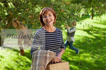 Portrait de femme souriante avec couverture et sac en verger de pommiers