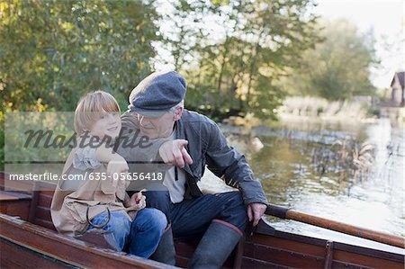 Grand-père et le petit-fils du bateau dans le lac