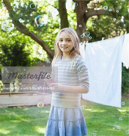 Porträt von smiling Girl bläst Seifenblasen im Hinterhof