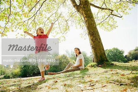 Mother watching exuberant daughter dancing under tree