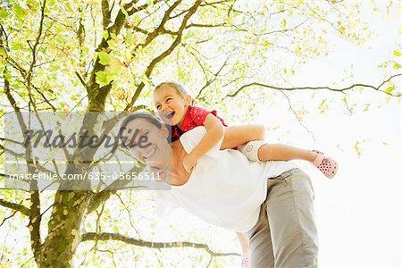 Mutter piggybacking Tochter unter Baum