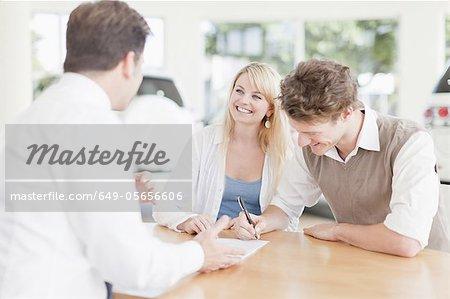 Customers signing at car dealership