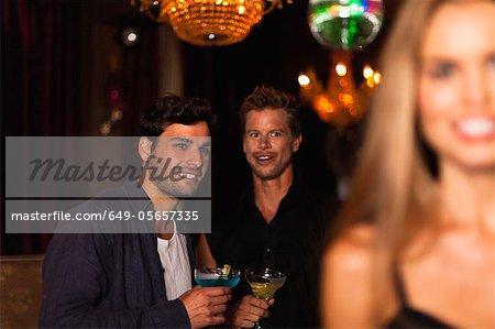 Männer, die Cocktails im Club lächelnd