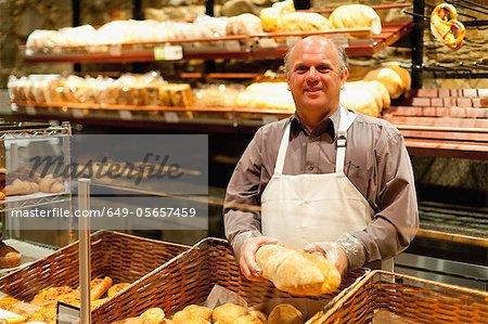 Lächelnd hält Laib Brot Bäcker