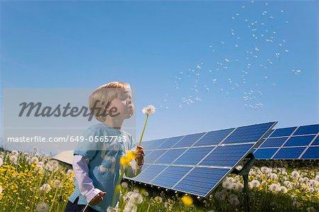 Junge im Feld mit Sonnenkollektoren