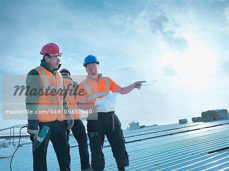 Travailleurs lire des bleus sur le toit