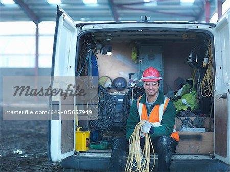 Travailleur de la construction holding enroulé de corde