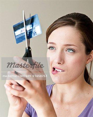 Femme, découpage de carte de crédit