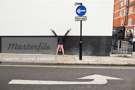 Handstand performant de femme sur la chaussée