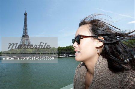 Gros plan de la femme et de la tour Eiffel en arrière-plan