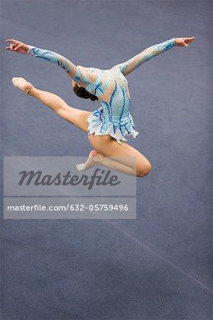 Female gymnast jumping in midair