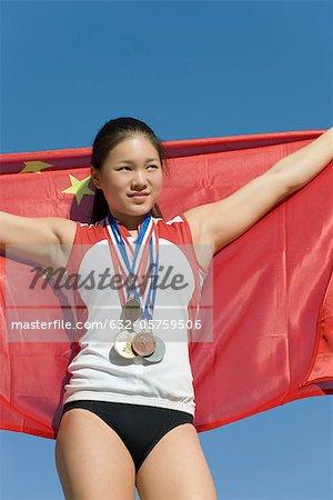 Female athlete on winner's podium, holding Chinese flag