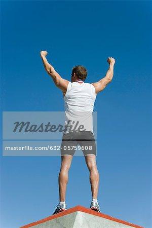 Männlicher Athlet stehend auf Podium des Siegers mit Arme heben Sieg, Rückansicht