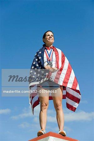 Athlète féminine étant honoré sur le podium, enveloppé dans le drapeau américain