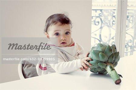Kleinkind mit frischen Artischocken