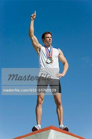 Männlicher Athlet stehend auf Podium des Siegers mit Hand heben Sieg