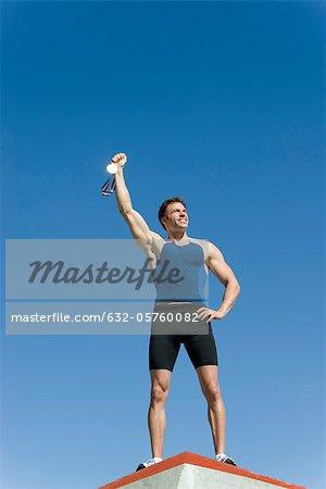 Male athlete on podium, holding up gold medal