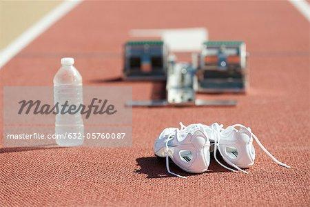 Chaussures de course et bouteille d'eau sur la piste de course, starting blocks en arrière-plan
