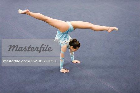 Female gymnast performing handstand