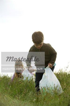 Children picking up trash in field