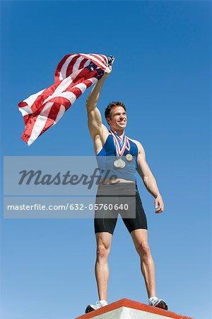 Male athlete on winner's podium, holding up American flag