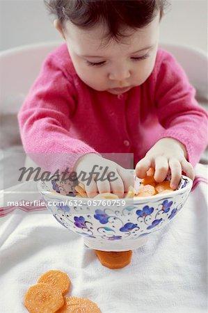 Kind spielt mit Schale mit Möhren